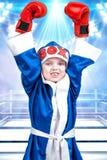 有红色手套的小男孩拳击手和长袍在圆环的背景中 冠军一点 大胜利 库存图片