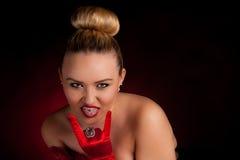 有红色手套的淘气年轻白肤金发的妇女延长他的舌头 库存照片