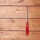 有红色把柄的十字形螺丝刀木表面上 库存图片