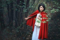 有红色披风的美丽的妇女在一个黑暗的森林里 免版税库存图片