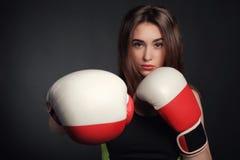 有红色拳击手套的美丽的妇女,黑背景 图库摄影