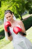 有红色拳击手套的新娘在公园 免版税库存图片