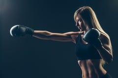有红色拳击手套的美丽的妇女,黑 免版税库存图片
