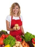 有红色提出土豆的围裙和新鲜蔬菜的主妇 免版税图库摄影