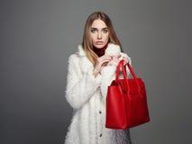 有红色提包的冬天美丽的妇女 秀丽毛皮的时装模特儿女孩 免版税库存照片