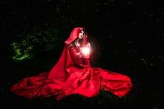 有红色斗篷和灯笼的美丽的妇女在森林 库存照片