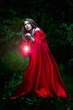 有红色斗篷和灯笼的美丽的妇女在森林 免版税图库摄影