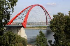 有红色曲拱的桥梁横跨河都市交通路线位于 库存照片