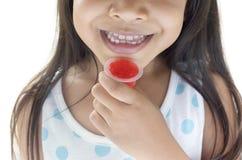 有红色果冻的愉快的矮小的亚裔女孩 库存图片