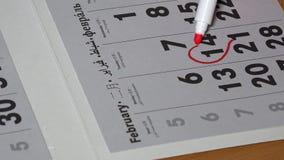有红色标志凹道的妇女手在日历2月14日的心脏形状 股票录像