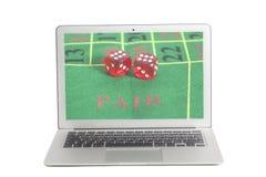 有红色模子的膝上型计算机在一个比赛表上在屏幕上的赌博娱乐场 免版税库存图片