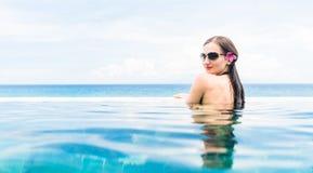 有红色比基尼泳装和花的妇女在无限水池的头发 免版税库存图片