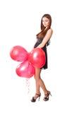 有红色气球的女孩在形式心脏 库存照片