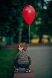 有红色气球的小滑稽的男孩 库存图片
