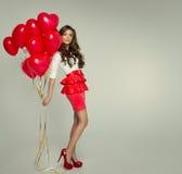 有红色气球的美丽的妇女 免版税库存图片