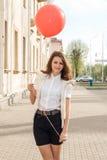 有红色气球的美丽的时尚女孩在街道上 免版税库存照片