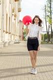 有红色气球的美丽的时尚女孩在街道上 库存照片