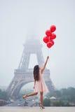 有红色气球的巴黎人妇女在埃佛尔铁塔前面 库存照片