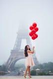 有红色气球的巴黎人妇女在埃佛尔铁塔前面 免版税库存照片