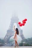 有红色气球的巴黎人妇女在埃佛尔铁塔前面 免版税库存图片