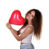 有红色气球的年轻愉快的女孩 库存照片