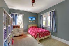 有红色河床和灰色墙壁的孩子卧室。 免版税库存照片