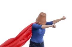 有红色海角的妇女超级英雄和在她的头的一个花盆 免版税图库摄影