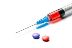 有红色液体的在白色的注射器和药片 免版税库存照片
