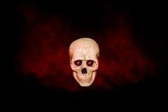 有红色烟的头骨在黑背景 免版税库存照片