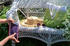 有红色片剂的妇女的手设法拍被编织的绿色袋子、草帽和太阳镜的构成照片在白色柳条 免版税库存图片