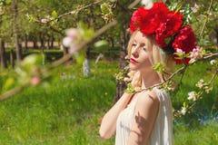 有红色牡丹的美丽的年轻柔和的典雅的年轻白肤金发的妇女在走在豪华的苹果树的白色女衬衫花圈 免版税图库摄影