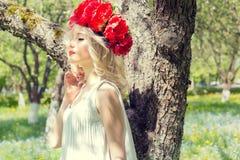 有红色牡丹的美丽的年轻柔和的典雅的年轻白肤金发的妇女在走在豪华的苹果树的白色女衬衫花圈 免版税库存图片