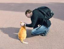 有红色猫的年轻人 免版税库存图片