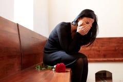 有红色玫瑰的哭泣的妇女在葬礼在教会里 免版税库存图片