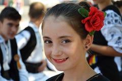 有红色玫瑰的女孩在她的头发 库存照片