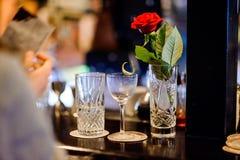 有红色玫瑰的水晶花瓶,一块空的玻璃和玻璃半满用水在酒吧柜台站立 库存图片