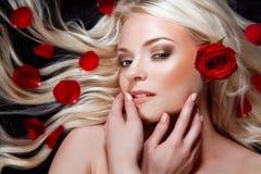 有红色玫瑰的美丽的女孩在她的金发。 免版税库存图片