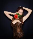 有红色玫瑰的肉欲的女孩在嘴 免版税图库摄影