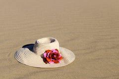 有红色玫瑰的草帽在沙子说谎 免版税库存照片
