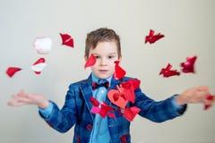 有红色玫瑰花瓣的可爱的小男孩 免版税库存照片