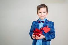 有红色玫瑰花瓣的可爱的小男孩 库存照片