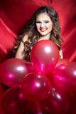 有红色球的美丽的典雅的愉快的少妇在有红色唇膏的手上 免版税库存图片