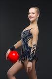 有红色球的Gymnastist女孩 免版税图库摄影
