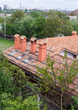 有红色瓦样式的新的砖房子和模件烟囱、塑料窗口和雨天沟 免版税库存照片