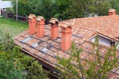有红色瓦样式的新的砖房子和模件烟囱、塑料窗口和雨天沟 免版税库存图片