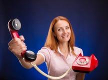 有红色电话的红头发人妇女 图库摄影