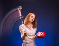 有红色电话的红头发人妇女 免版税库存照片