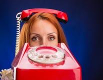 有红色电话的红头发人妇女 免版税库存图片