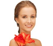有红色百合花的可爱的妇女 免版税库存图片