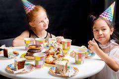 有红色的坐在桌上和enjoing蛋糕的女孩和黑色头发 免版税库存图片